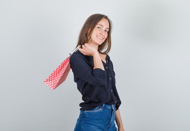 黒のシャツ、ジーンズのショートパンツで紙袋を保持し、陽気に見える若い女性