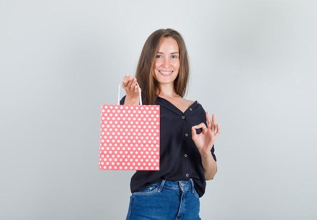 黒のシャツ、ジーンズのショートパンツでokサインと陽気に見える紙袋を保持している若い女性