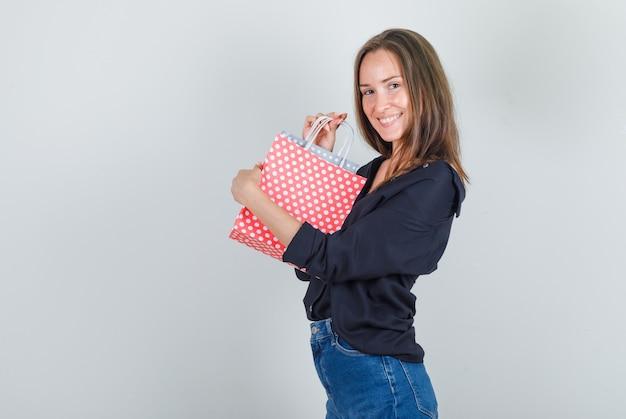 黒のシャツ、ジーンズのショートパンツで紙袋を保持し、陽気に見える若い女性。