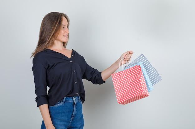 黒のシャツ、ジーンズのショートパンツで紙袋を保持し、うれしそうに見える若い女性