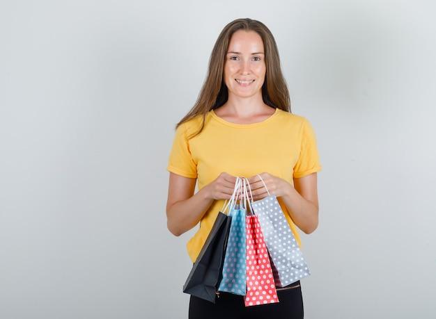 黄色のtシャツ、黒のズボンで紙袋を保持し、陽気に見える若い女性