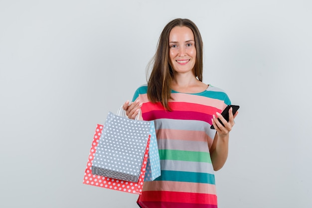 Young woman holding paper bags and smartphone in t-shirt and looking cheerful. front view.