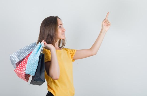 黄色のtシャツ、パンツで指で紙袋を持って、嬉しそうに見える若い女性。