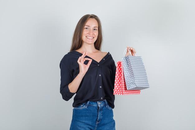 黒のシャツ、ジーンズのショートパンツでokサインと紙袋を保持し、幸せそうに見える若い女性
