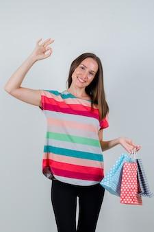 Молодая женщина, держащая бумажные пакеты с хорошо подписывается в футболке, штанах и выглядит счастливой, вид спереди.