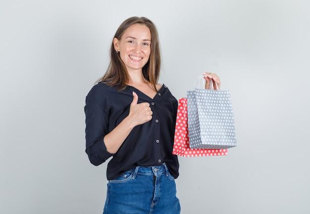黒のシャツ、ジーンズのショートパンツと幸せそうに見える親指で紙袋を保持している若い女性