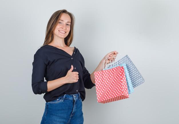 黒のシャツ、ジーンズのショートパンツで親指で紙袋を保持し、うれしそうに見える若い女性