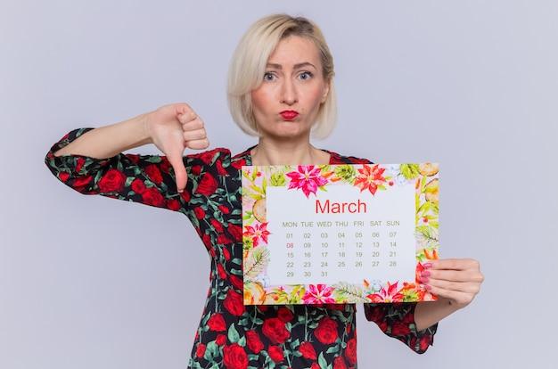 Giovane donna che tiene il calendario cartaceo del mese di marzo