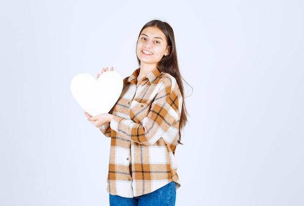 白い壁に紙のハート型のカードを保持している若い女性。