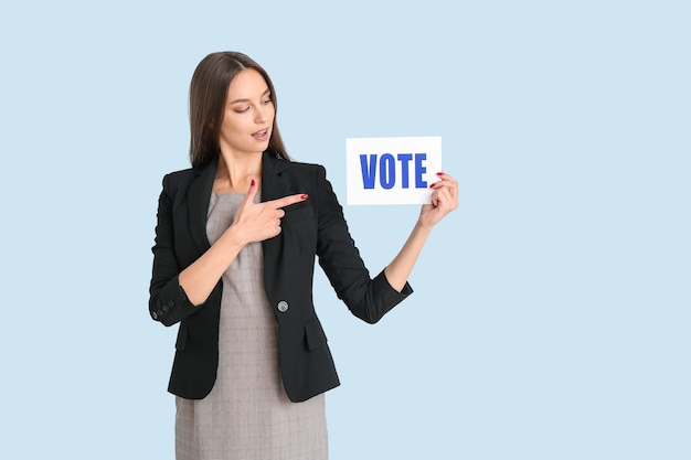 Young woman holding paper with text vote on color background