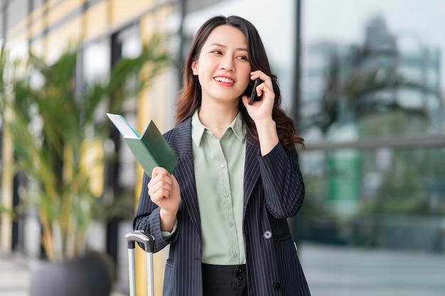Молодая женщина, держащая паспорт и билет на самолет в аэропорту