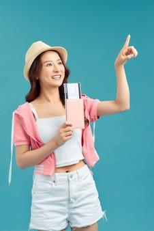 Молодая женщина, держащая паспорт, кредитную карту. улыбающаяся девушка-путешественница на синем фоне.