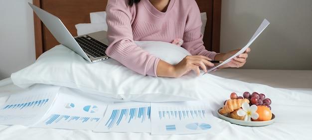 ペンを持っている若い女性は、ラップトップのビデオ会議を使用し、自宅からベッドの仕事で果物を食べる