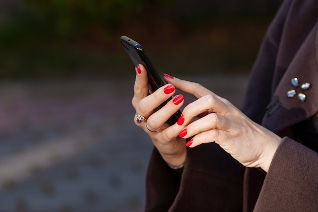 Young woman holding phone in hands with beautiful red manicure. close up picture outdoor. copy space
