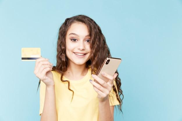 スタジオで携帯電話を持ってオンラインショッピングをしている若い女性。