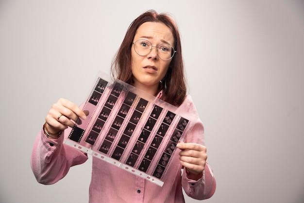 Giovane donna in possesso di un nastro fotografico su un bianco. foto di alta qualità