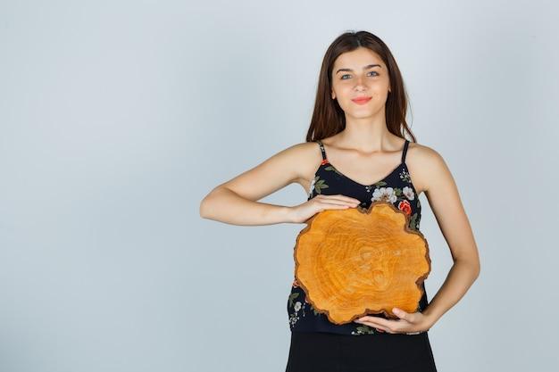 Молодая женщина держит кусок дерева в блузке, юбке и выглядит веселым. передний план.