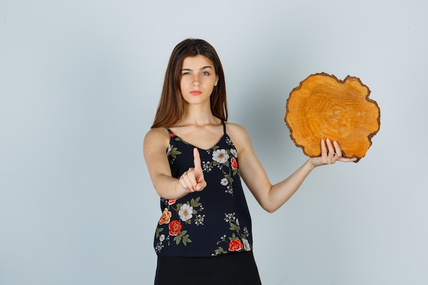 젊은 여성이 나무 조각을 들고 블라우스, 치마를 입고 진지한 표정을 하고 있는 짧은 몸짓을 보여줍니다.