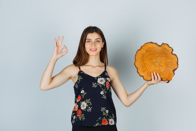 Giovane donna che tiene in mano un pezzo di legno, mostra un gesto ok in camicetta e sembra allegra, vista frontale.