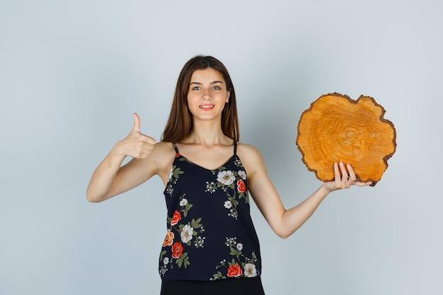 Giovane donna che tiene un pezzo di legno, mostra il pollice in camicetta e sembra allegro. vista frontale.