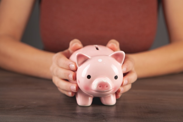 Young woman holding a piggy bank by the table