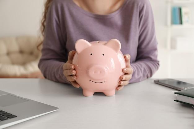 屋内で貯金箱を保持している若い女性、クローズ アップ。お金の節約の概念