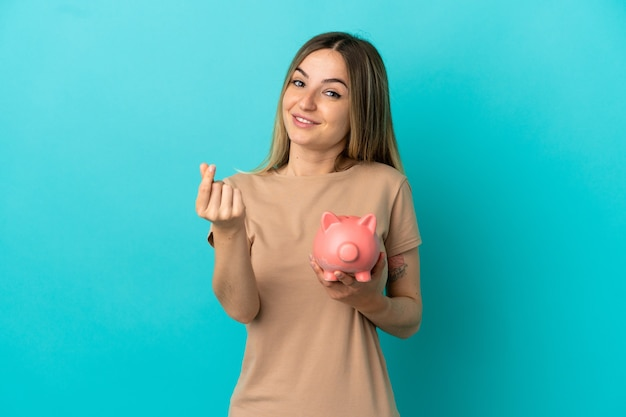 Young woman holding a piggybank over isolated blue background making money gesture