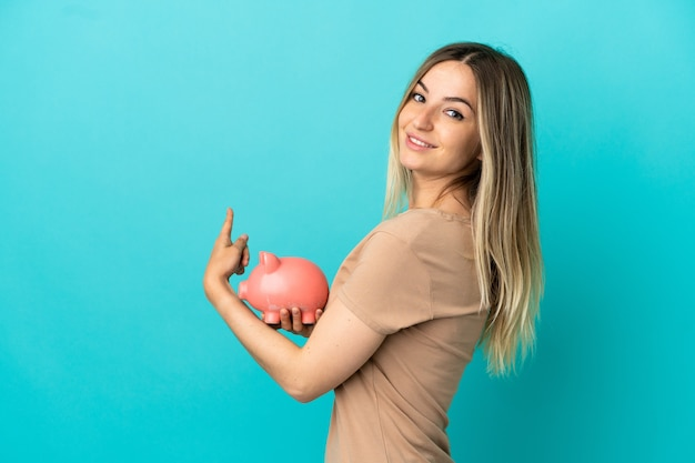Young woman holding a piggybank over isolated blue background pointing back