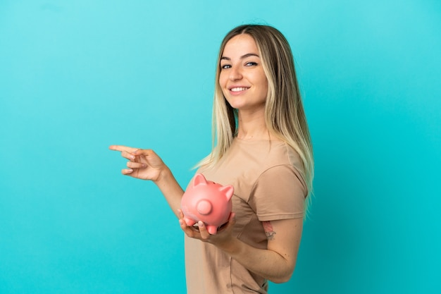 Young woman holding a piggybank over isolated blue background pointing finger to the side