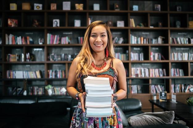 Молодая женщина с кучей книг в кафе
