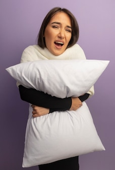 枕を持っている若い女性は混乱し、非常に心配しています