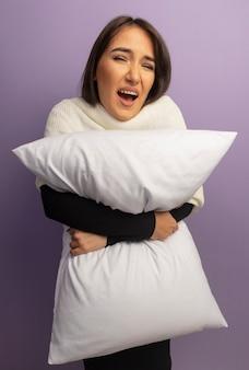 Giovane donna che tiene il cuscino confuso e molto ansioso