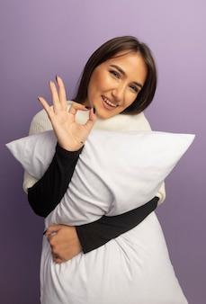 Молодая женщина, держащая подушку, улыбается со счастливым лицом, показывая знак ок