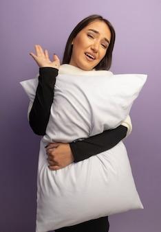 手で手を振って幸せな顔で笑顔の枕を保持している若い女性