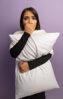 Giovane donna che tiene cuscino unghie mordaci stressate e nervose