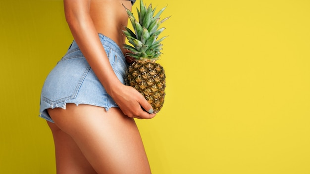 Young woman holding a pineapple in her hand on color background