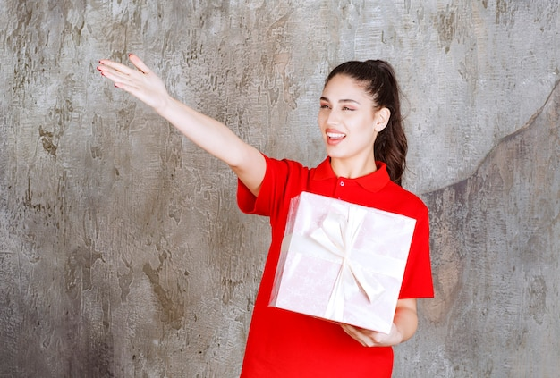 Young woman holding a pink gift box wrapped with white ribbon and pointing at someone.