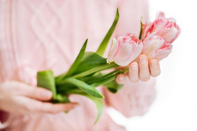 흰색 바탕에 분홍색 튤립을 들고 있는 젊은 여성. 초상화, 근접 촬영, 복사 공간, 선택적 초점을 흐리게 합니다.