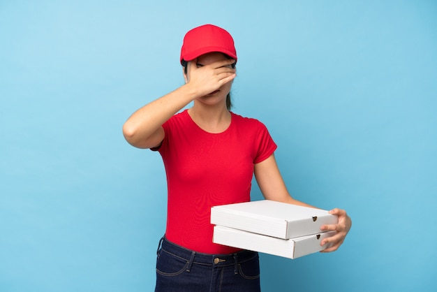 Young woman holding a pizza over isolated pink wall covering eyes by hands