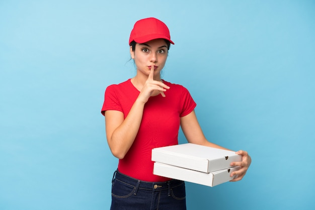 Young woman holding a pizza over isolated pink wall doing silence gesture