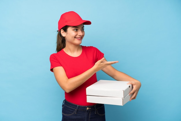 Young woman holding a pizza over isolated pink wall extending hands to the side for inviting to come