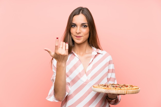 Young woman holding a pizza over isolated pink wall inviting to come with hand. happy that you came