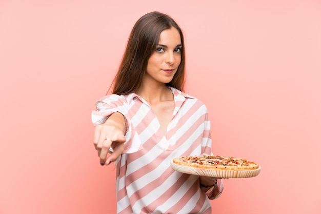 Young woman holding a pizza over isolated pink wall points finger at you with a confident expression