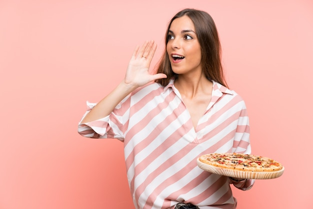 Young woman holding a pizza over isolated pink wall shouting with mouth wide open