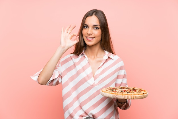 Young woman holding a pizza over isolated pink wall showing ok sign with fingers