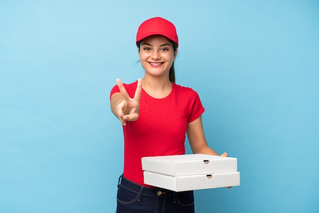 Young woman holding a pizza over isolated pink wall smiling and showing victory sign