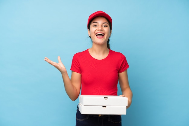 Young woman holding a pizza over isolated pink wall unhappy and frustrated with something
