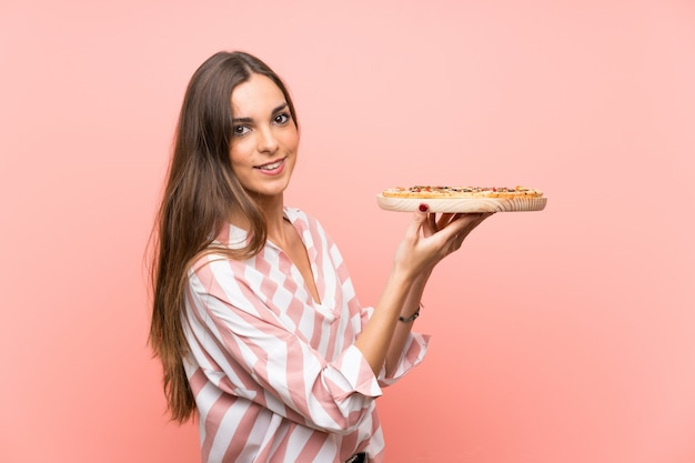 Young woman holding a pizza over isolated pink wall