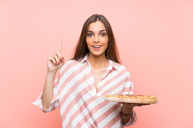 Young woman holding a pizza pointing up a great idea