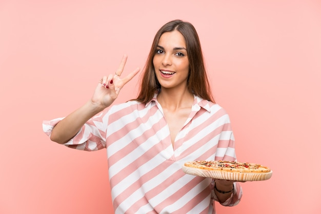 Young woman holding a pizza smiling and showing victory sign